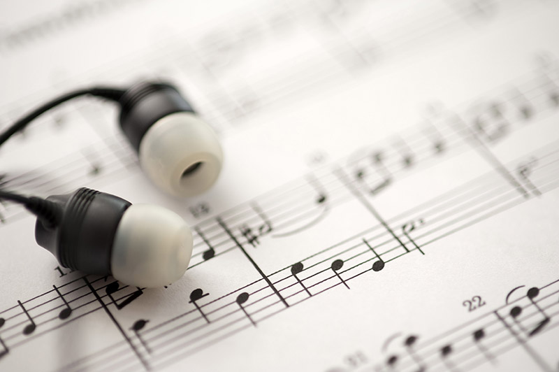 sheet music and earbud headphones